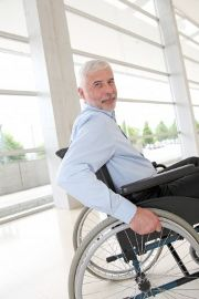 A man in a wheelchair smiles at the camera as he wheels out of shot