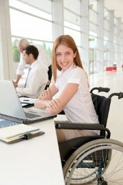 A woman in a wheelchair looks up from a laptop computer and smiles at the camera