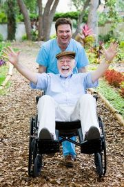 A very happy old man in a wheelchair is pushed by a smiling helper